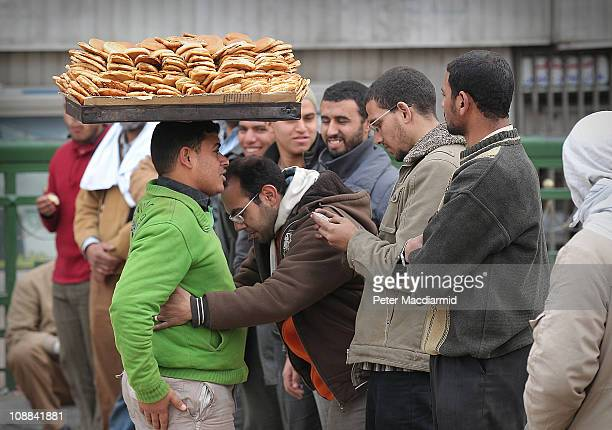Antigovernment protesters search a boy selling bread as he enters Tahrir Square on February 5 2011 in Cairo Egypt Thousands of the demonstrators...