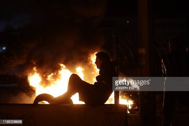 Anti-government protesters set tyres aflame as they cut off a section of the Beirut-Byblos highway in the Lebanese coastal city of Byblos on January...