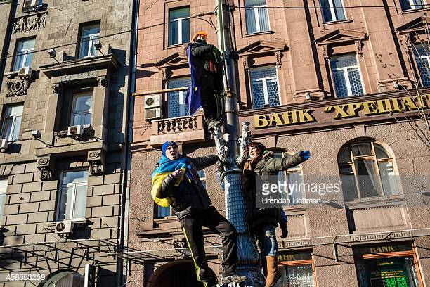 Antigovernment protesters shout from a lamp post near Independence Square on December 14 2013 in Kiev Ukraine Thousands of people have been...