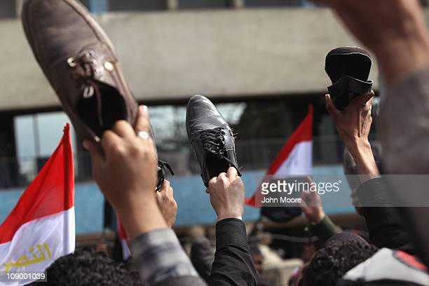 Antigovernment protesters show the bottoms of their shoes in a traditional Islamic insult in front of the national television headquarters on...