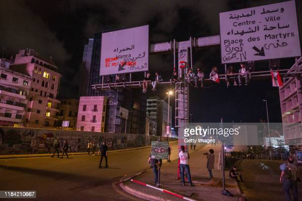 Antigovernment protesters sit on a road sign on the Ring Bridge which had earlier been the scene of a violent confrontation between demonstrators and...