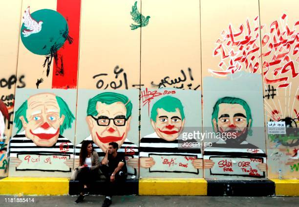 Antigovernment protesters sit under graffiti depicting Lebanese politicians with joker faces sprayed on a wall in downtown Beirut on November 12 2019...