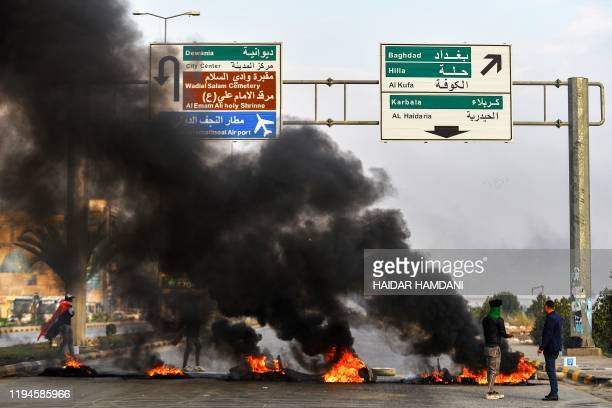 Anti-government protesters stand before a tire fire at a make-shift roadblock during a demonstration in the central Iraqi holy shrine city of Najaf...