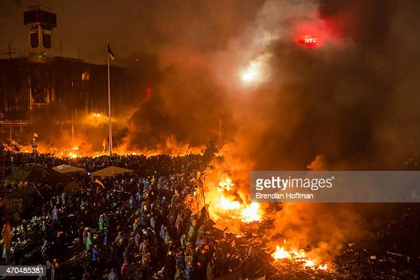 Antigovernment protesters stand behind a line of burning tires and debris on Independence Square on February 19 2014 in Kiev Ukraine After several...