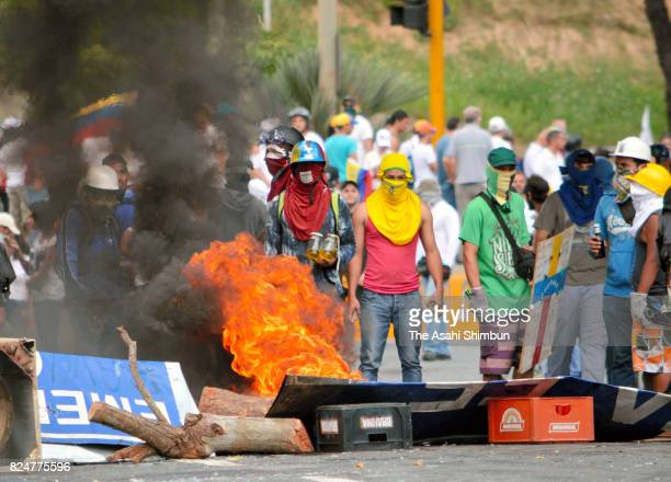 Antigovernment protesters stand near a barricade as they refuse the new Constituent Assembly Election on July 30 2017 in Caracas Venezuela
