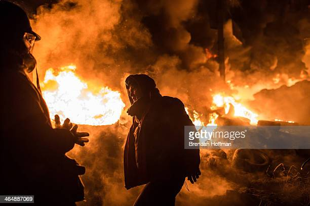 Antigovernment protesters stand near burning tires during clashes with police on Hrushevskoho Street near Dynamo stadium on January 25 2014 in Kiev...