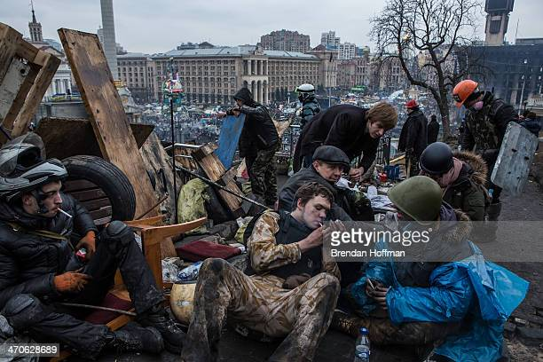 Antigovernment protesters take a break to smoke cigarettes on a hill above Independence Square on February 20 2014 in Kiev Ukraine After several...