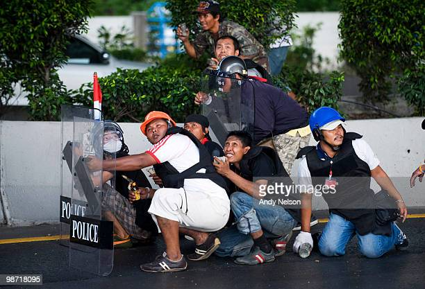 Antigovernment protesters take cover as they clash with police and military on April 28 2010 in Bangkok Thailand Troops clashed with protesters after...