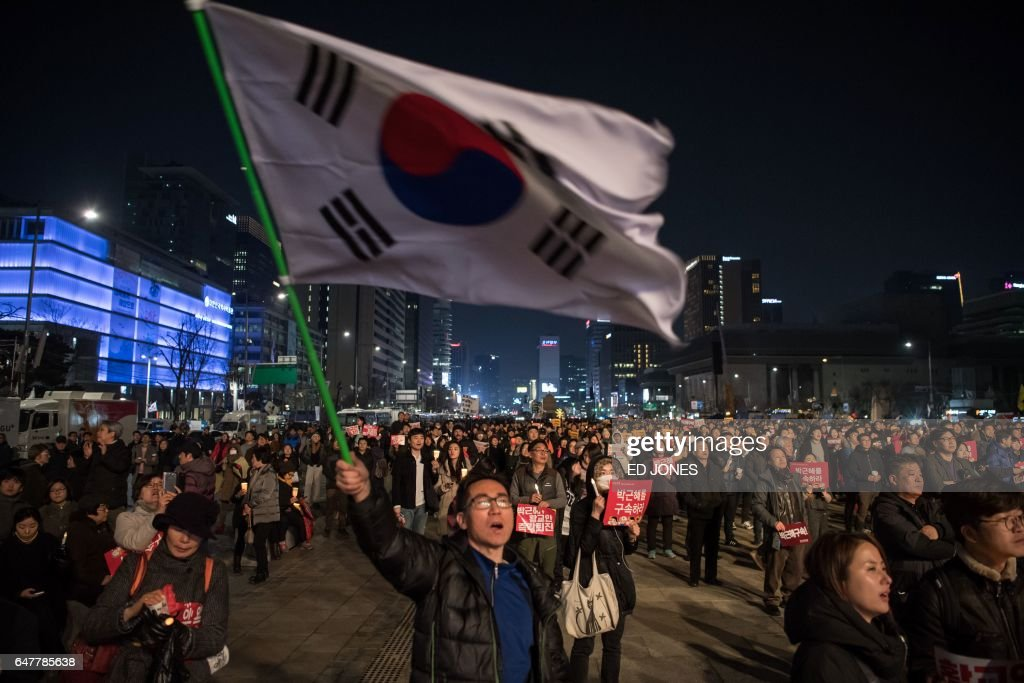 Anti-government protesters take part in a march in Seoul on March 4, 2017. Tens of thousands of South Korean protesters held rival mass rallies over the impeachment of President Park Geun-Hye as judges prepare to rule on the scandal that has rocked the country. / AFP PHOTO / Ed JONES