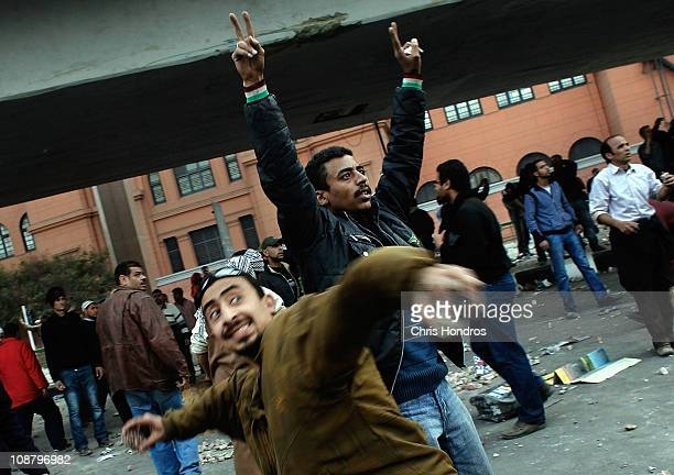 Antigovernment protesters taunt and throw rocks at progovernment supporters near a highway overpass on the edge of Tahrir Square the afternoon of...