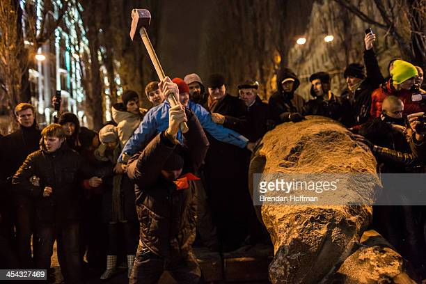 Antigovernment protesters use a sledge hammer to destroy a statue of Russian communist revolutionary leader Vladimir Lenin on December 8 2013 in Kiev...