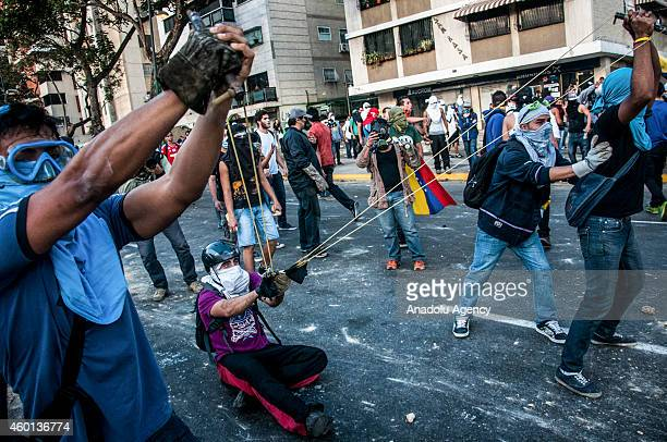Antigovernment protesters use a slingshot to hurl stones at riot police in Caracas Venezuela on March 3 2014 Antigovernment protests keep going on in...