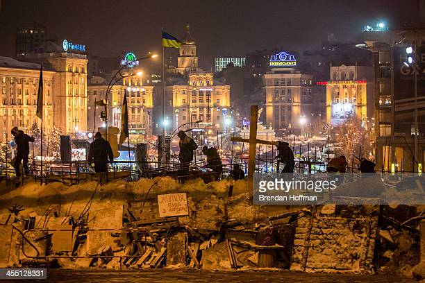 Antigovernment protesters use snow to reinforce a barricade blocking street access to Independence Square known as the Euromaidan on December 11 2013...