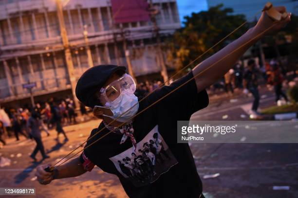 Anti-Government protesters uses a slingshot against police during a protest calling for the resignation of prime minister Prayut Chan-O-Cha over the...