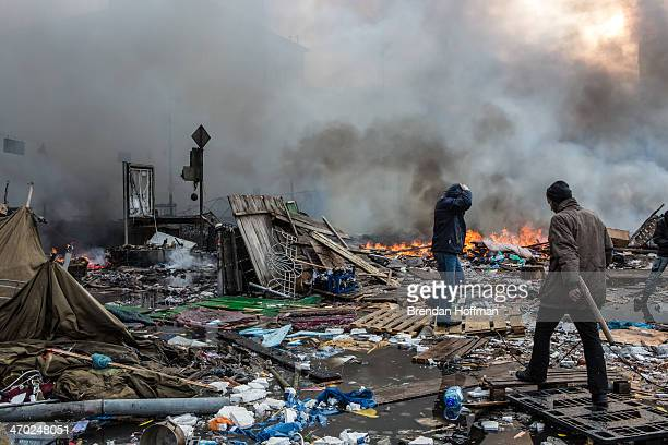 Antigovernment protesters walk amid debris and flames near the perimeter of Independence Square known as Maidan on February 19 2014 in Kiev Ukraine...