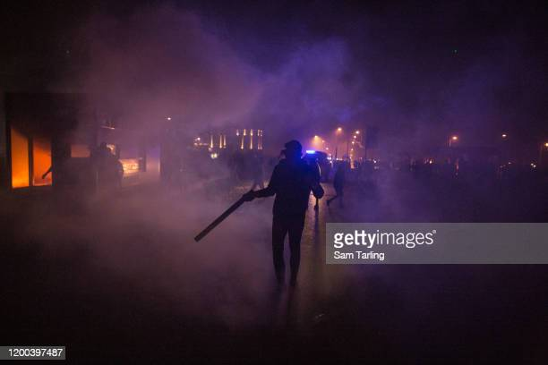 Anti-government protesters walk through clouds of tear gas as they clash with riot police, on January 18 in Beirut, Lebanon. According to the Red...