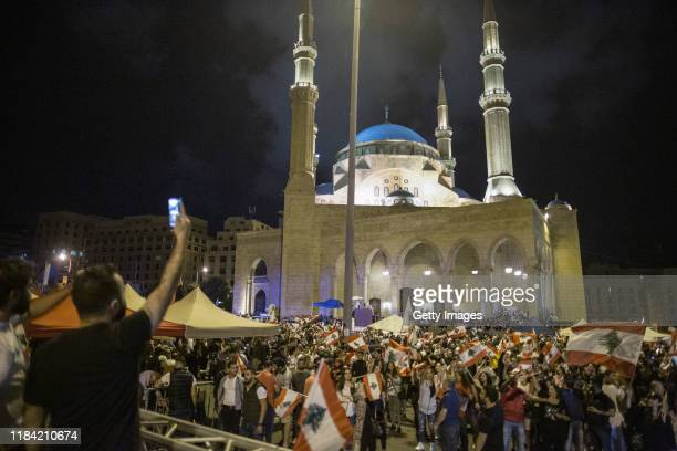 Antigovernment protesters wave Lebanese flags in Martyrs' Square on October 29 2019 in Beirut Lebanon Dozens of rioters who wanted to reopen Beirut's...