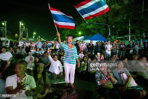 Antigovernment protesters wave national flags during a rally at Democracy Monument on November 26 2013 in Bangkok Thailand The Prime Minister of...