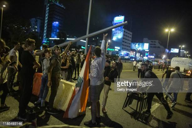 Antigovernment protesters wave through cars during an hourlong amnesty in which they opened one lane to traffic on the highway entering Beirut on...
