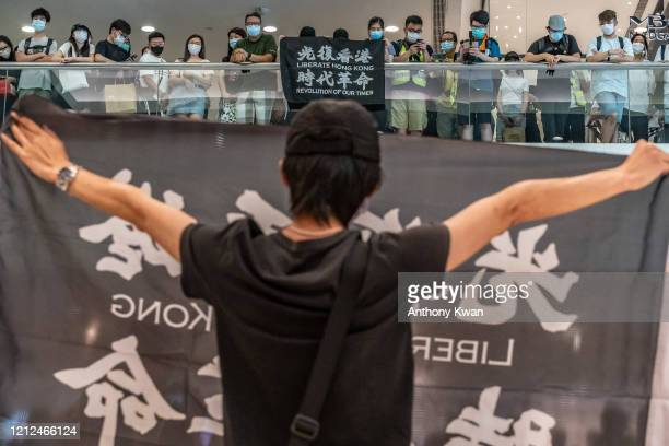 Antigovernment protesters wearing protective masks hold Liberate Hong Kong Revolution Of Our Times banners during a demonstration at a shopping mall...