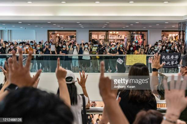 Antigovernment protesters wearing protective masks sing songs and make gestures during a demonstration at a shopping mall on May 10 2020 in Hong Kong...
