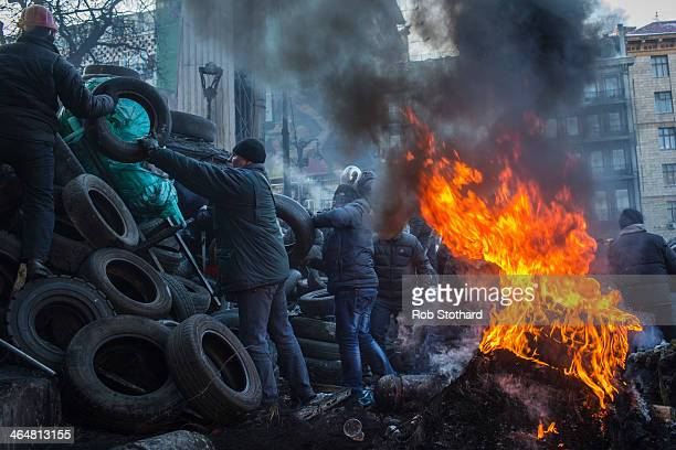 Antigovernment protestors add tyres to a barricade near Dynamo Stadium on January 24 2014 in Kiev Ukraine Talks to resolve the political stalemate in...