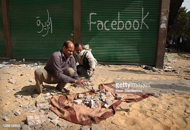 Antigovernment protestors break paving stones for the defence of Tahrir Square in front of a shop spray painted with the word Facebook on February 4...
