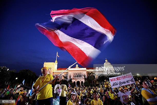 Antigovernment protestors wave the national flag at Government House on August 26 2008 in Bangkok Thailand Thousands of antigovernment protestors...