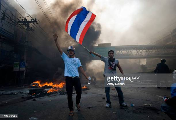 Antigovernment red shirt protester flies the Thai flag as a fellow protester encourages other to advance up a street as the violence in central part...