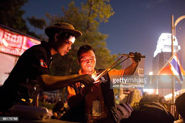 Antigovernment 'Red Shirt' protesters use a sling shot to launch a fire cracker towards Thai security forces from inside their encampment on May 13...