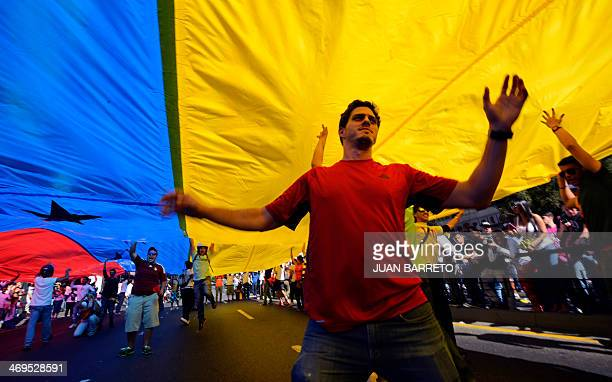 Antigovernment students marcha under a huge flag during a protest in front of the Venezuelan Judiciary building in Caracas on February 15 2014...