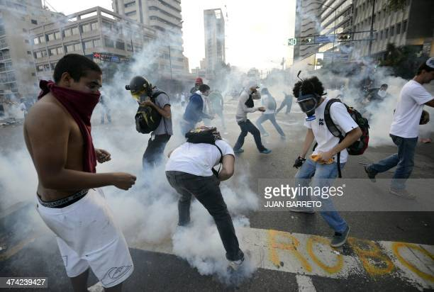 Antigovernment students throw tear gas bombs back to riot policemen during a protest in Caracas on February 22 2014 Hundreds of thousands of...