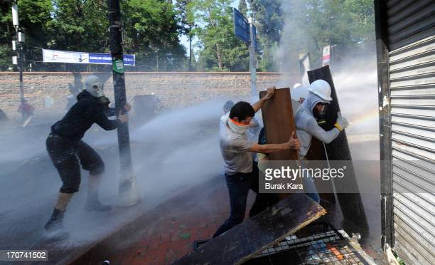 Anti-government use boarding to protect themselves from water cannon fired by police in the Kurtulus district on June 16, 2013 in Istanbul, Turkey....