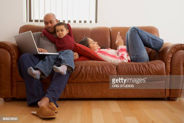 antiguan man using laptop in living room with family - palm sunday photos et images de collection