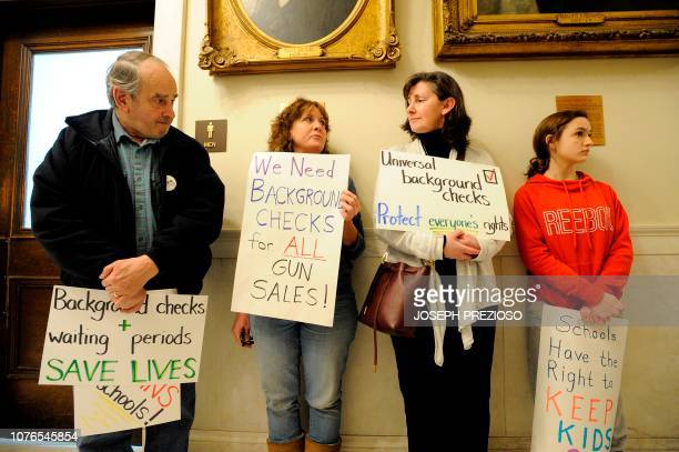 Antigun supporters stand in the hallway during the opening day of the House of Representatives at the New Hampshire State House where the House will...