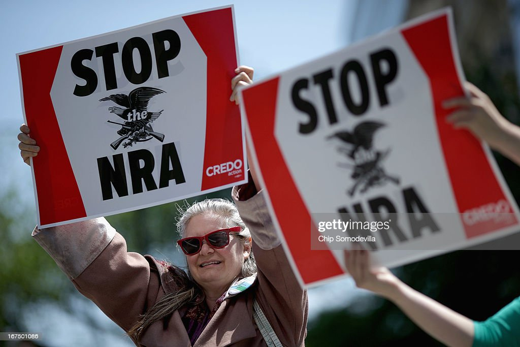 Anti-gun violence demonstrators, including Robin Diener (L), hold signs condeming the National Rifle Association during a protest in McPhearson Square April 25, 2013 in Washington, DC. Angry with the U.S. Senate's failure to pass an expansion of background checks for people wanting to buy guns, the demonstrators attempted to deliver faux bank checks and crime scene photos to a handful of lobbying firms that represent the NRA.
