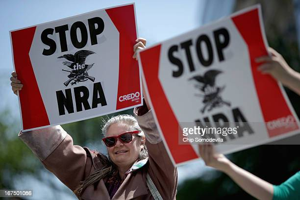 Antigun violence demonstrators including Robin Diener hold signs condeming the National Rifle Association during a protest in McPhearson Square April...