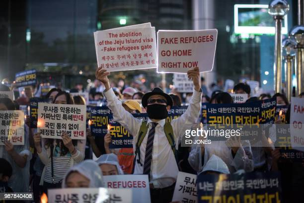 Antiimmigration activists attend a protest against a group of asylumseekers from Yemen in Seoul on June 30 2018 South Korea will tighten its refugee...