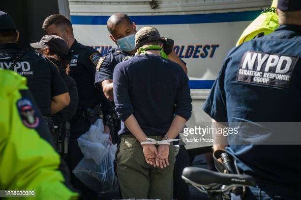 Anti-Immigration and Customs Enforcement protester arrested and handcuffed after a standoff with NYC Police in Times Square.