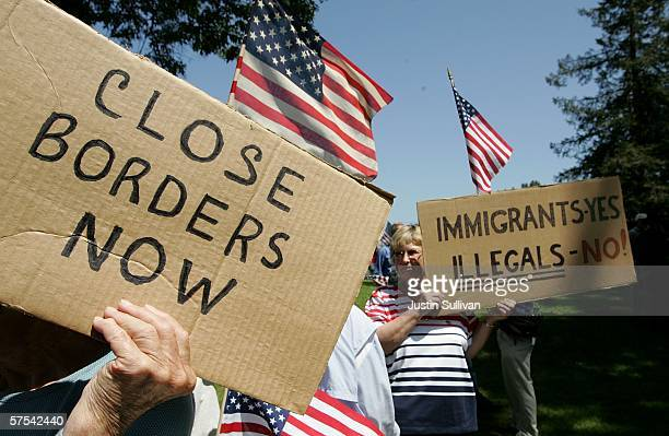 Antiimmigration demonstrators hold signs and American flags during an antiimmigration rally May 5 2006 in Santa Clara California Dozens of...