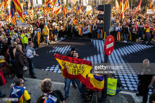 Antiindependence supporter waiving a Spanish flag with the words 'long live the King' protesting against Catalan proindependence demonstrators during...