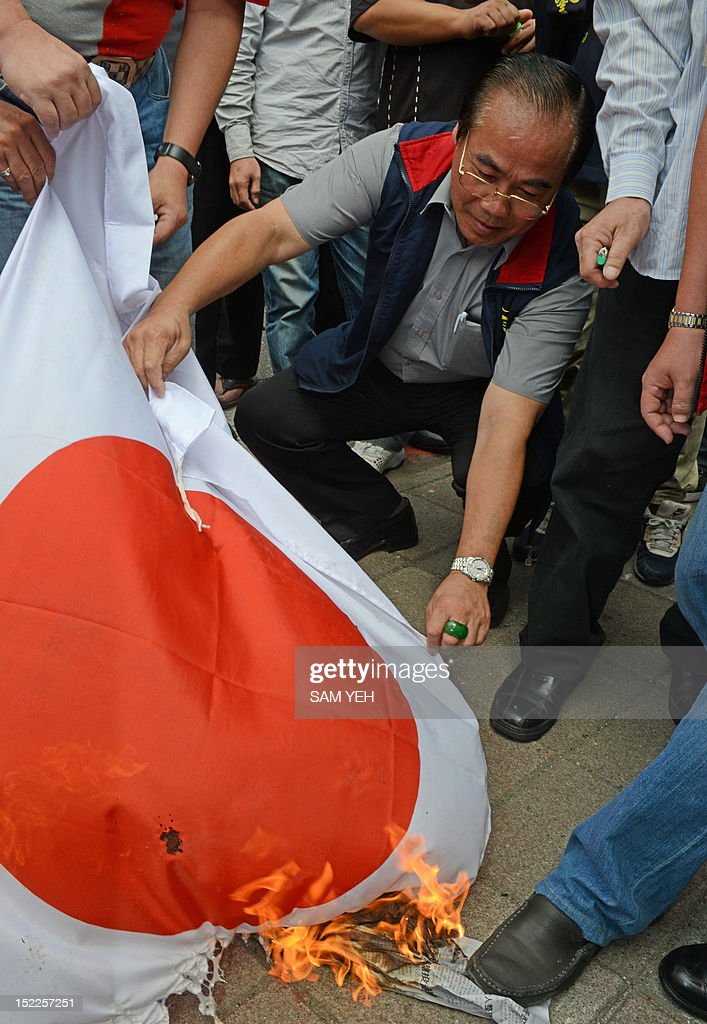 Anti-Japan activists set fire to a Japanese flag during a protest in front of the parliament building in Taipei over a group of disputed islands, known as the Diaoyu islands in Chinese or the Senkaku islands in Japanese, on September 18, 2012. A group of Taiwanese fishermen are planning to sail this week to the disputed archipelago in the East China Sea at the centre of a territorial row among Taiwan, China and Japan, a politician said. AFP PHOTO / Sam Yeh