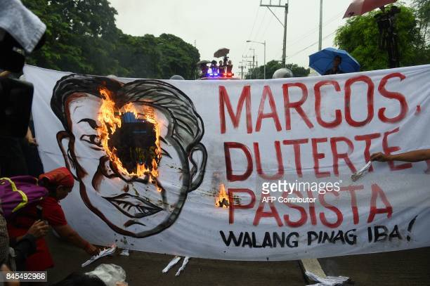 AntiMarcos protesters burn a banner with a representation of a composite portrait of late dictator Ferdinand Marcos and President Rodrigo Duterte...
