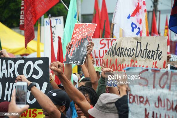 AntiMarcos protesters raise clenched fists during a demonstration held on the 100th birthday of late dictator Ferdinand Marcos near the Heroes...
