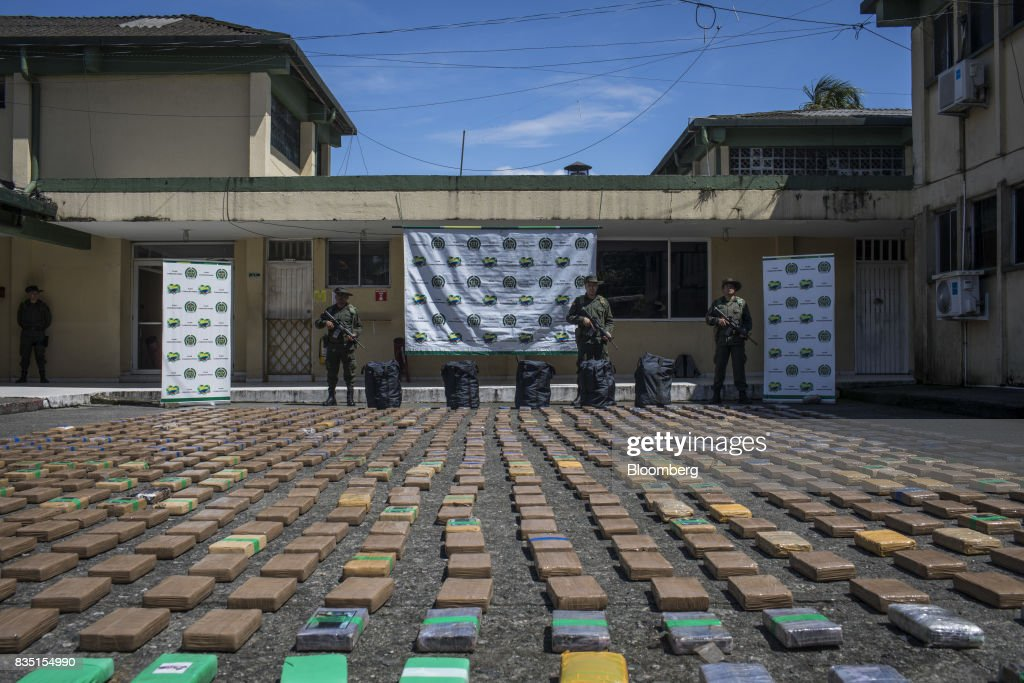 Anti-narcotics police officers stand guard over packages of cocaine, seized from inside a shipping container at the Buenaventura port, in Buenaventura, Colombia, on Thursday, Aug. 10, 2017. The United Nations Office of Drugs and Crime (UNODC) released a report stating that coca crops in Colombia has increased over fifty percent in one year. The Trump administration has been putting pressure on Colombia to curb the flow of drugs into the U.S. Photographer: Nicolo Filippo Rosso/Bloomberg via Getty Images