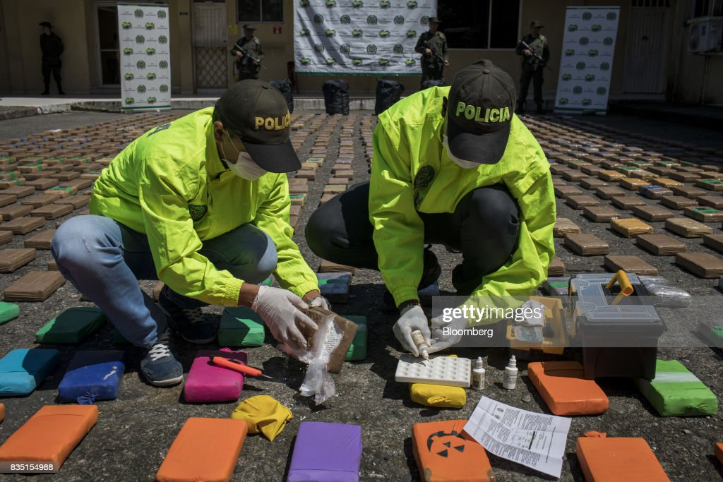 Anti-narcotics police officers test packages of cocaine, seized from inside a shipping container at the Buenaventura port, in Buenaventura, Colombia, on Thursday, Aug. 10, 2017. The United Nations Office of Drugs and Crime (UNODC) released a report stating that coca crops in Colombia has increased over fifty percent in one year. The Trump administration has been putting pressure on Colombia to curb the flow of drugs into the U.S. Photographer: Nicolo Filippo Rosso/Bloomberg via Getty Images