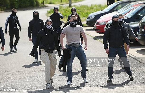 AntiNazi activists taunt supporters of the farright NPD political party marching on May Day in Dierkow district on May 1 2014 in Rostock Germany...