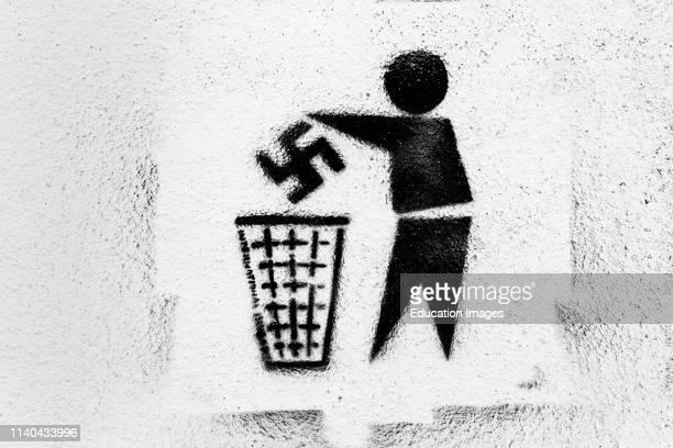 AntiNazi graffiti Swastika being thrown into rubbish bin Photographed in Tarifa Spain