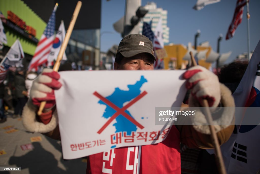 Anti-North Korea protesters shout slogans near the Olympic stadium prior to the opening ceremony of the Pyeongchang 2018 Winter Olympic Games in Pyeongchang on February 9, 2018. / AFP PHOTO / Ed JONES