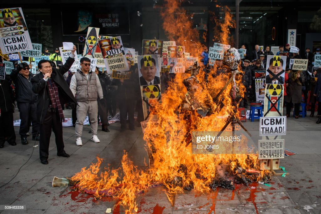 TOPSHOT - Anti-North Korean activists burn placards showing North Korean leader Kim Jong-Un as they protest the latest nuclear test and rocket launch by Pyongyang, in Seoul on February 11, 2016. South Korea said it would suspend operations at the Kaesong joint industrial complex in North Korea to punish Pyongyang for its latest rocket launch and nuclear test. AFP PHOTO / Ed Jones / AFP / ED